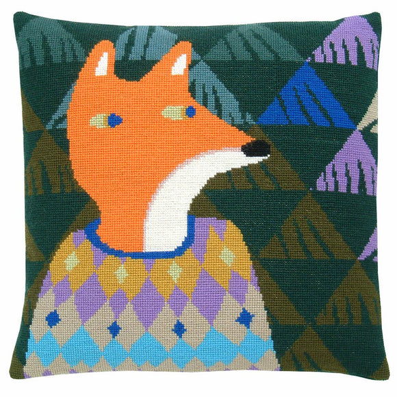 Cross stitch cushion cover with a fox wearing a yellow, purple, blue and fawn diamond-patterned jumper on a background of dark green, moss green, pale green, blue and purple triangles.
