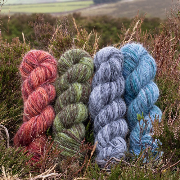 4 skeins of The Croft Wild Shetland nestled im heather out in the countryside. From left to right thebshades are Fired Earth, Rolling Hills, Stormy Skies and Turning Tides