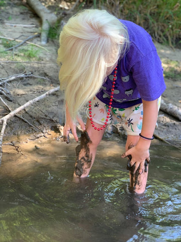 A muddy Pearl playing in the river at coral farms summer camp