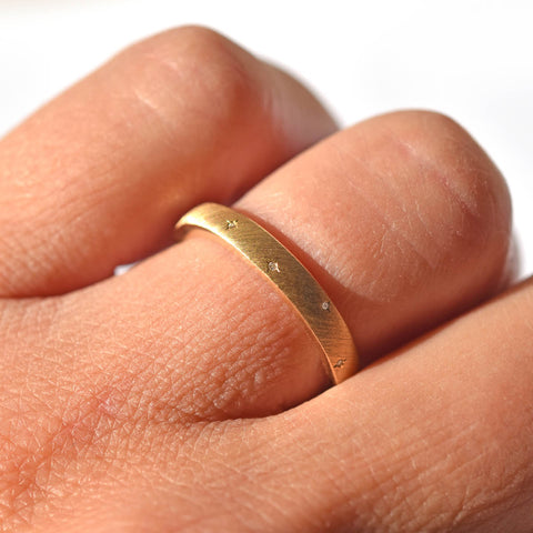 Brushed natural gold wedding band with embedded diamonds