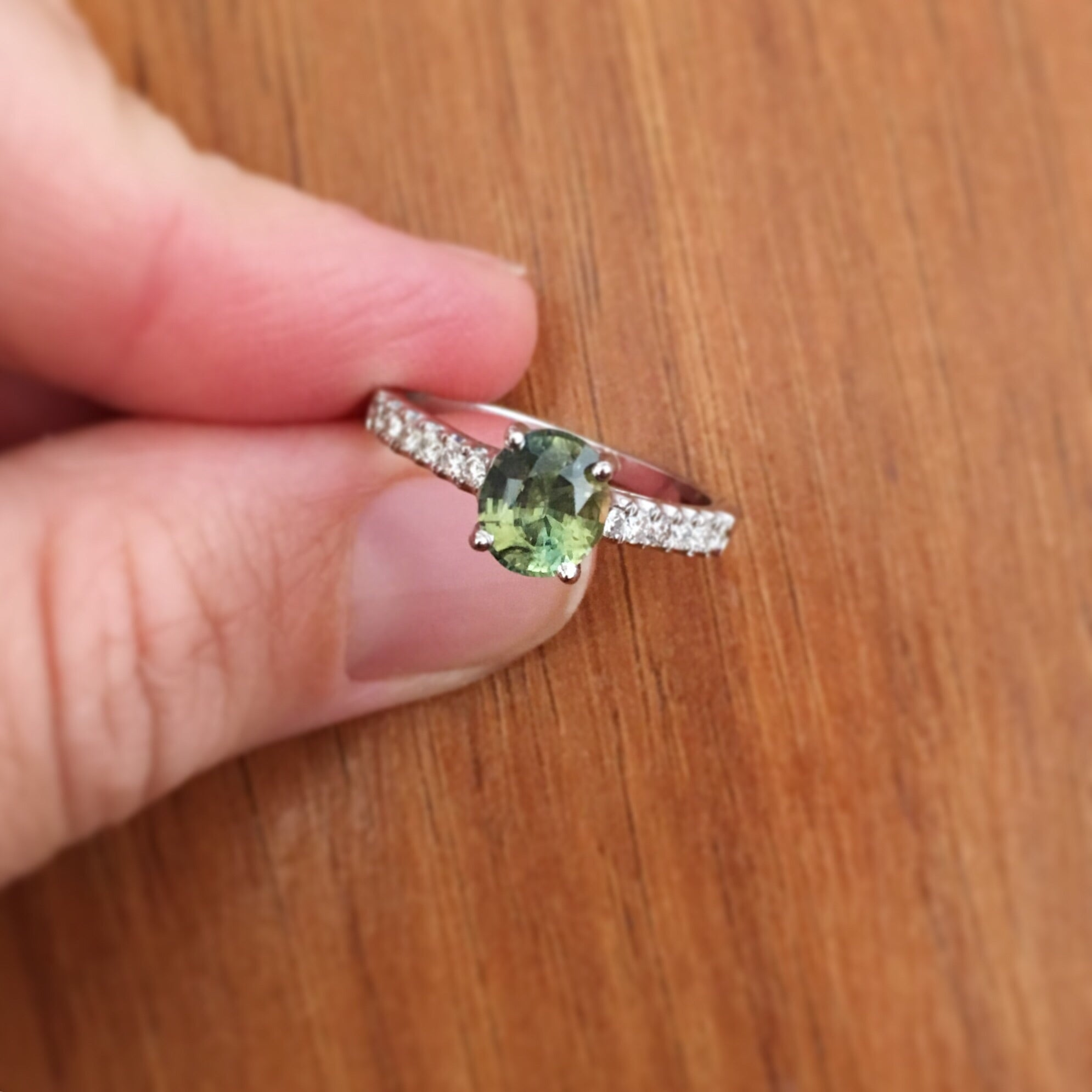 Oval jungle green sapphire held by four prongs with melee