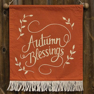 "An orange fabric wall hanging with cream colored fringe. Screen printed with ""Autumn Blessings"" in a cursive script in the middle of the wall hanging."