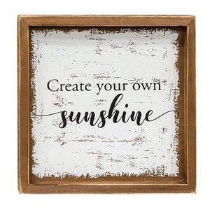 "Rustic wood sign with brown mitered wood frame. Distressed white background with the inspirational quote ""Create your own sunshine"" in script."