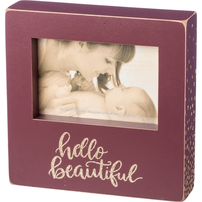Wooden box picture frame that holds a portrait style photo. Box frame is maroon with Hello Beautiful wrote in gold glitter.