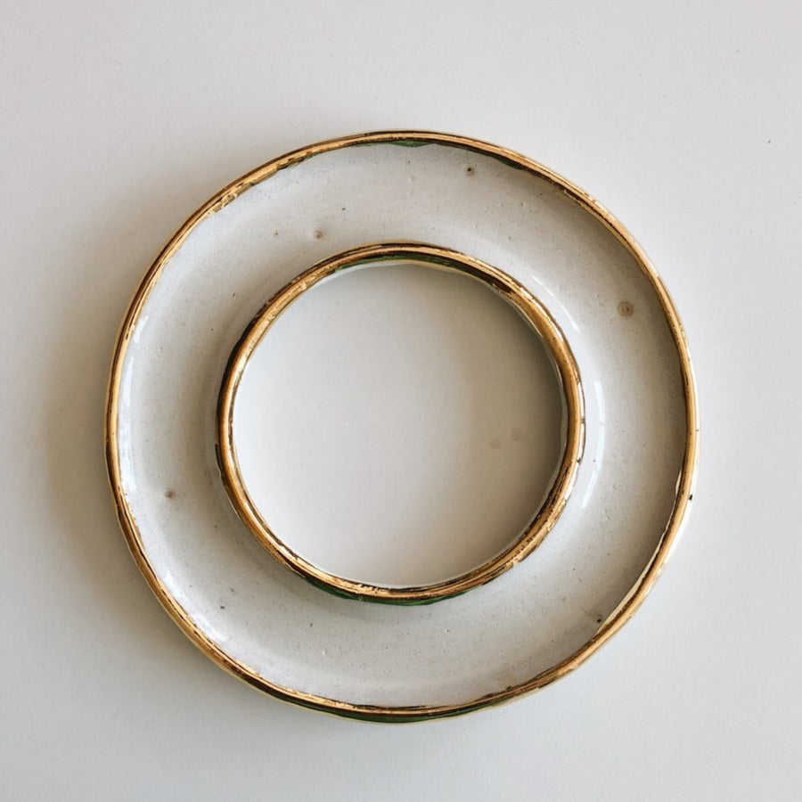 An overview shot of the porcelain and gold donut dish, a shallow dish with gold rims, photographed against a white tabletop