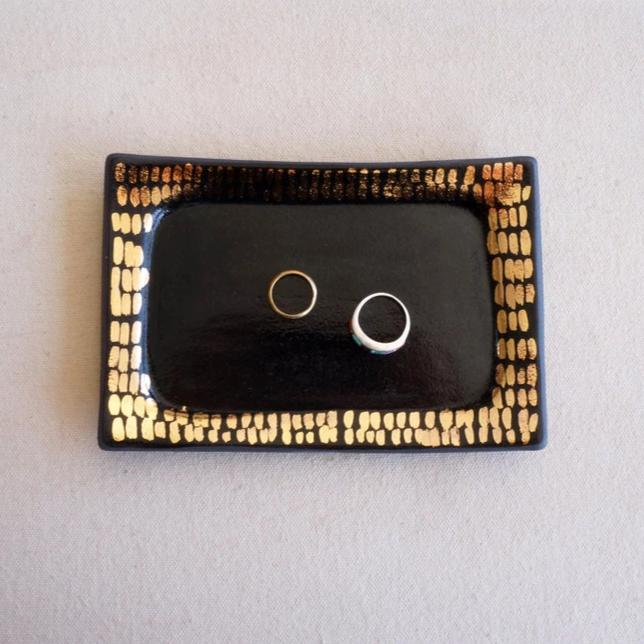 Black and gold rectangular ceramic tray that holds rings and other small pieces of jewelry