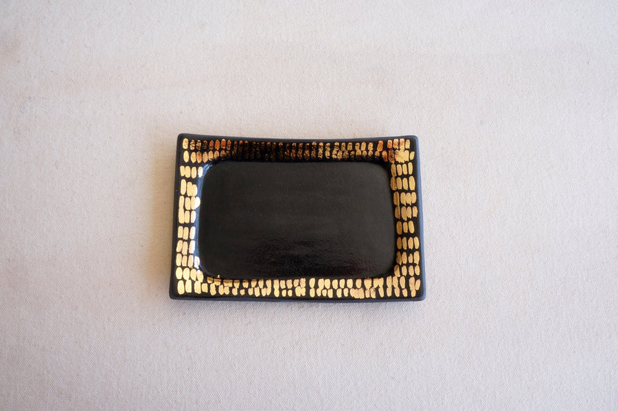 Rectangular ceramic tray in black and gold designed to hold jewelry and other small items