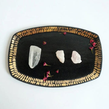 Rose and crystal quartz stones with flower petals sitting on a black ceramic tray, embellished with gold dash marks around the edges.