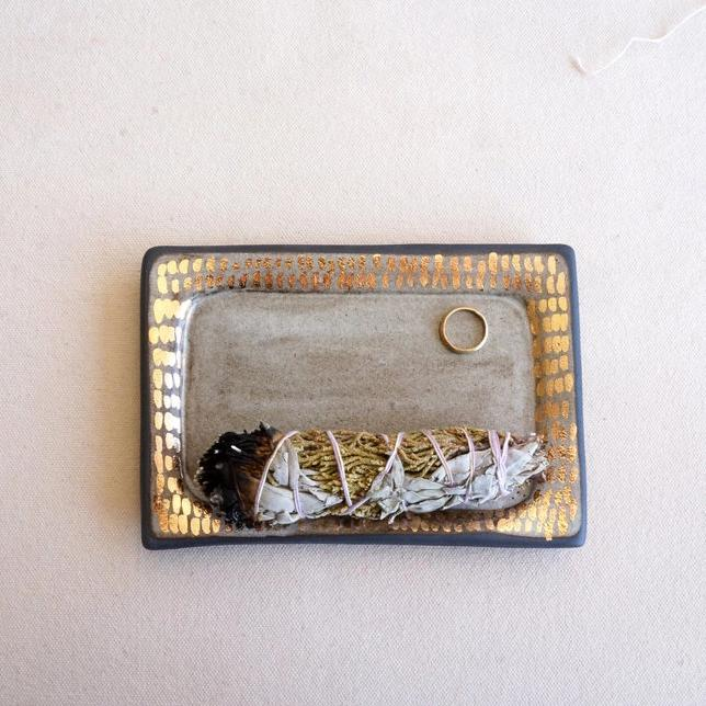 A handmade and hand painted ceramic tray made by The Object Enthusiast, photographed here with a small golden ring and a burned bundle of sage incense positioned on the tray, glazed in white with gold accents