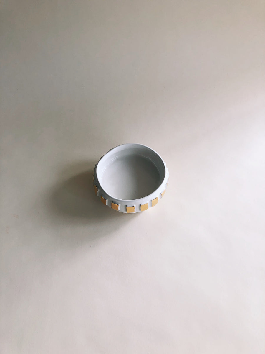 A view from the top of this handmade sculptural bowl with gold on the outside and white on the inside