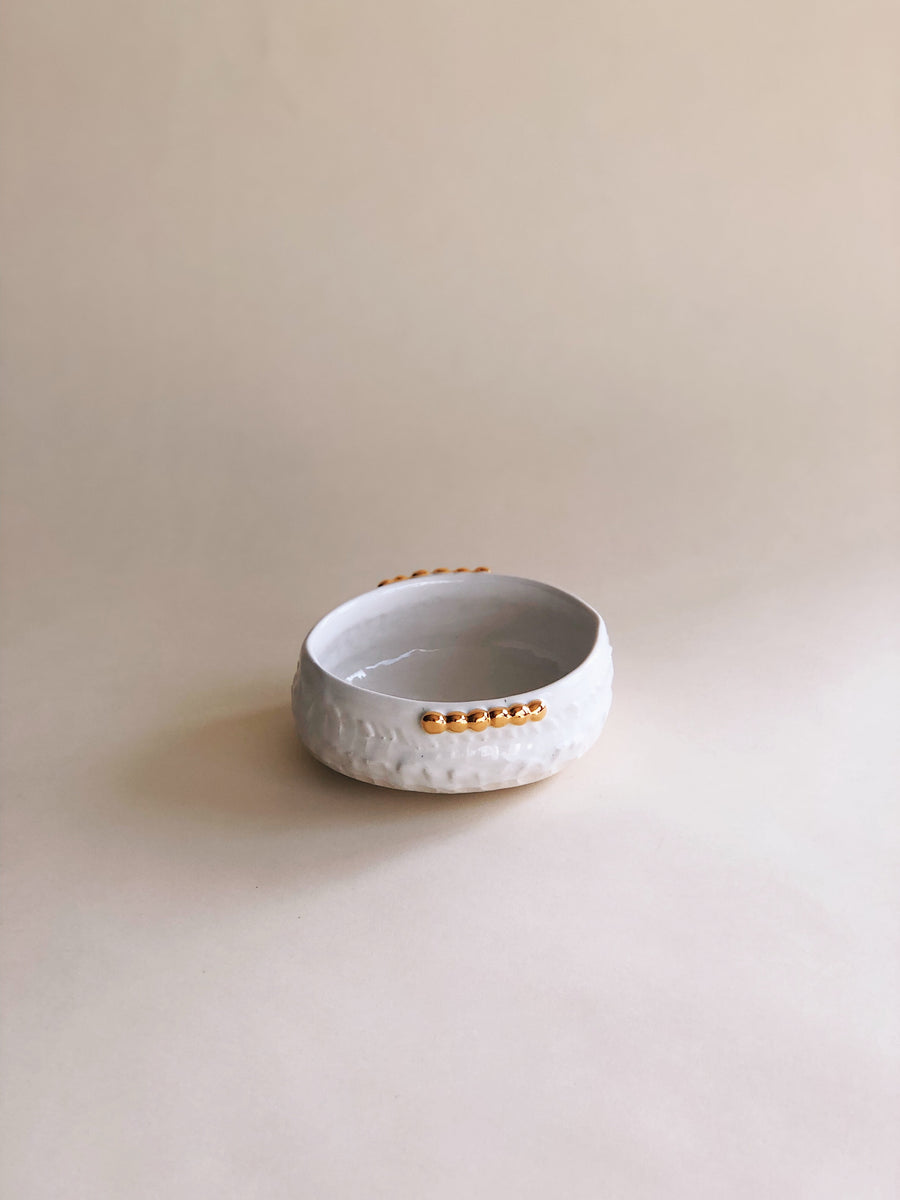 An alternative view of the handcrafted porcelain white and gold beaded vessel, sitting against a neutral tan backdrop