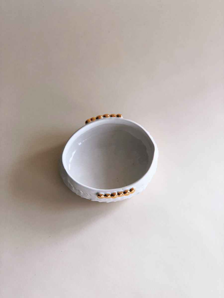 A white and gold beaded ceramic dish, shot from above to show both sides of the gold beaded accents at the rim, shot against a neutral backdrop
