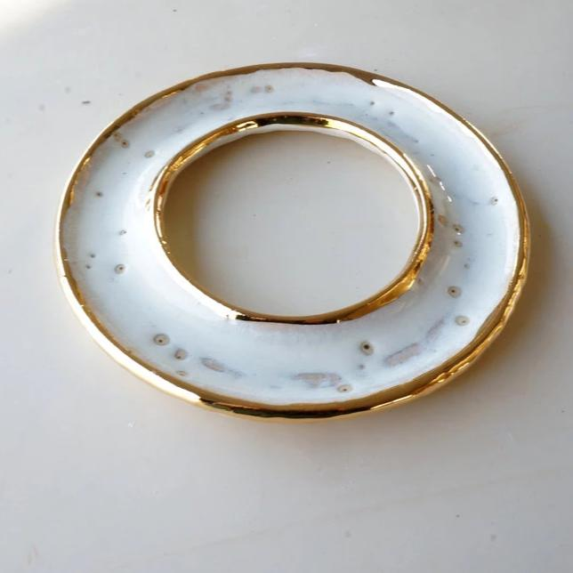A white and gold ceramic porcelain dish, handmade in the shape of a donut white gold edges, photographed on a white tabletop