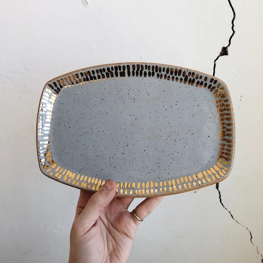 A hand holding a handmade stoneware ceramic tray, slightly oval shaped, with a speckled gray texture and gold accents. It's being held against a white wall with a large crack in it