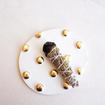 A flat, white and gold polka dotted incense trivet sits on a neutral background with a burned bundle of incense sitting on the trivet