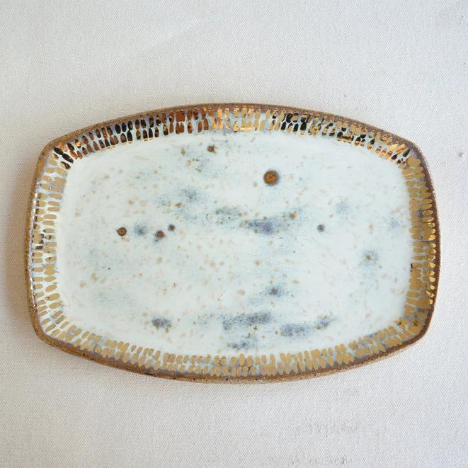 An overhead shot of a cream colored oval ceramic stoneware handmade tray, glazed in a glossy iridescent white with gold accents along the edges