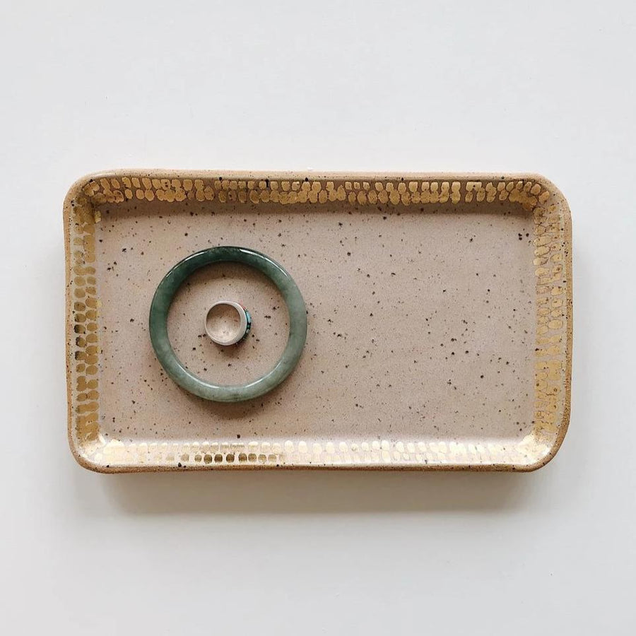 A handmade ceramic stoneware rectangular tray sits on a white table while holding a bracelet and a ring, the tray is intended for jewelry and other small collectibles, it's a speckled light pink color with some gold accents