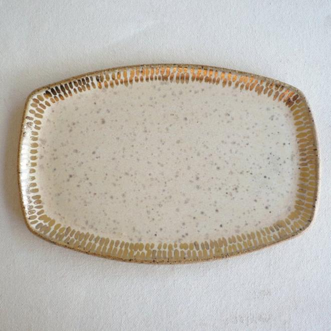 A speckled stoneware ceramic tray sitting on a neutral background, the tray is a light cream with gold around the edges