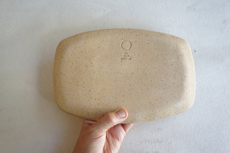 A hand holding a speckled stoneware ceramic tray, this photo shows the backside of the tray to convey the color and texture of the clay body it is made from