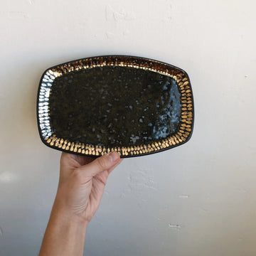 A hand holding a speckled black and gold vanity tray against a white wall, handmade by The Object Enthusiast