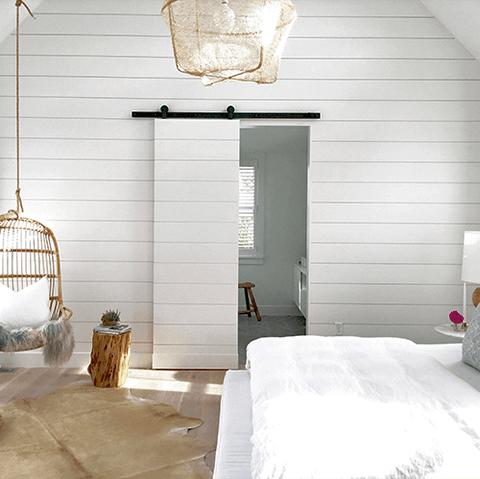 6. White narrow sliding barn door on a white room