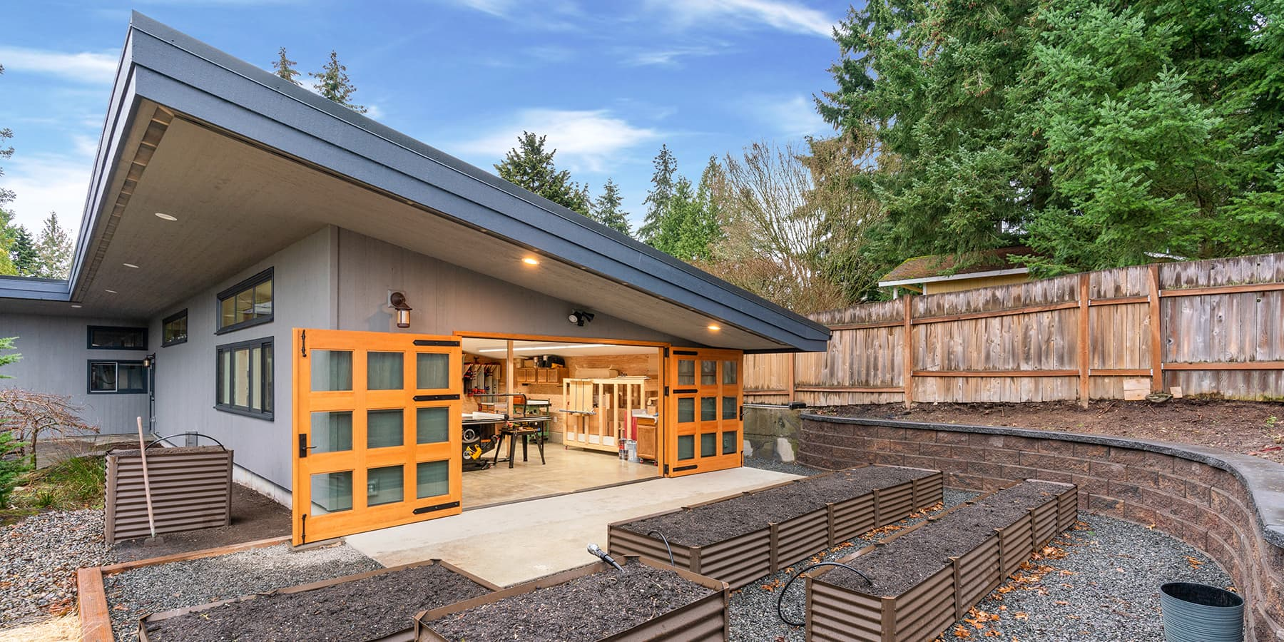 McIntyre Furniture woodshop exterior view. Image highlights set of Vertical Grain Douglas Fir Carriages Doors designed by RealCraft. The carriage doors have 9 individual glass panes on each door and strap hinges were installed for aesthetics.