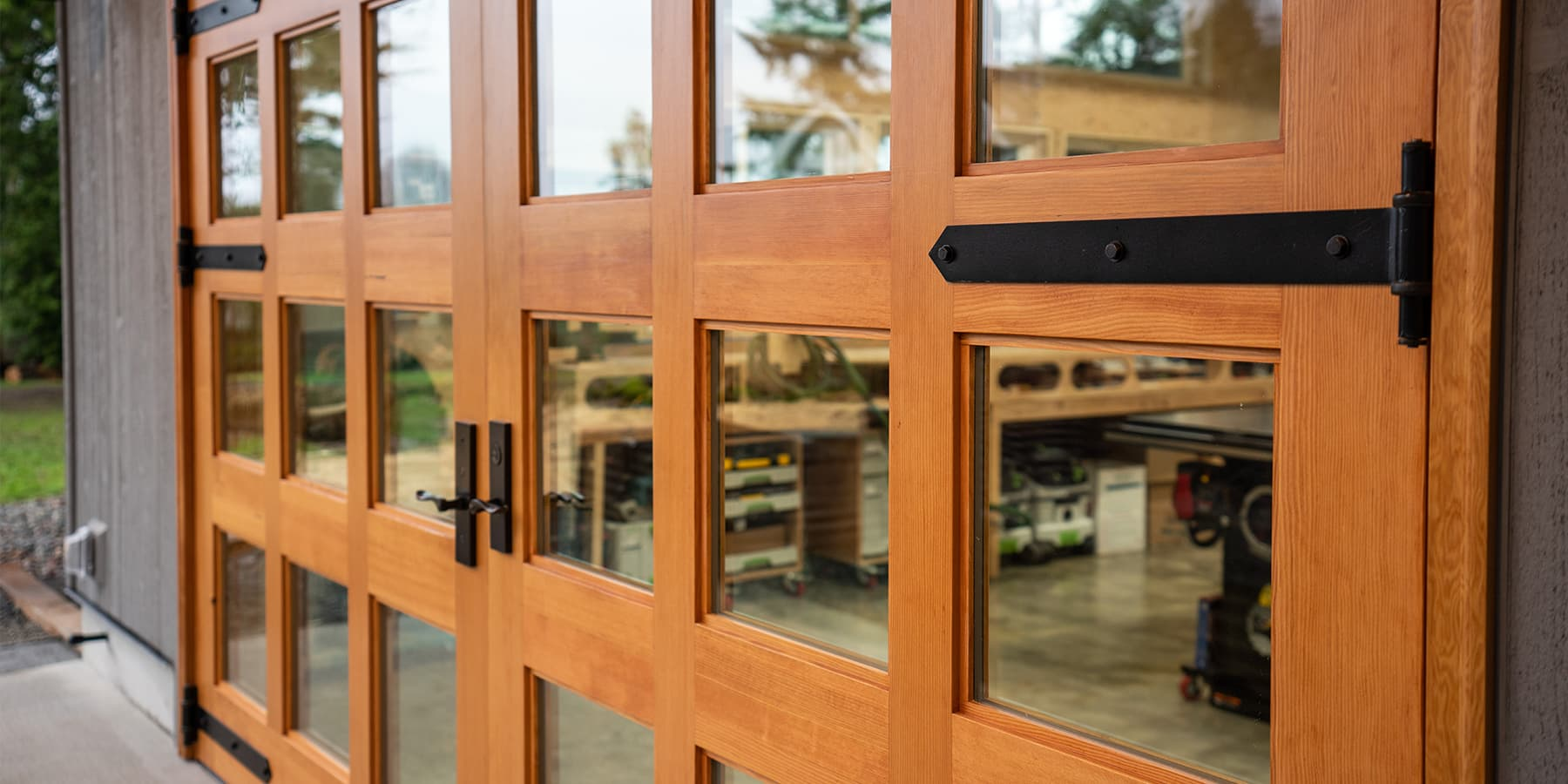 Vertical Grain Douglas Fir Carriage Door image close up highlighting wood grain, strap hinges, and glass panes. Door designed by RealCraft.