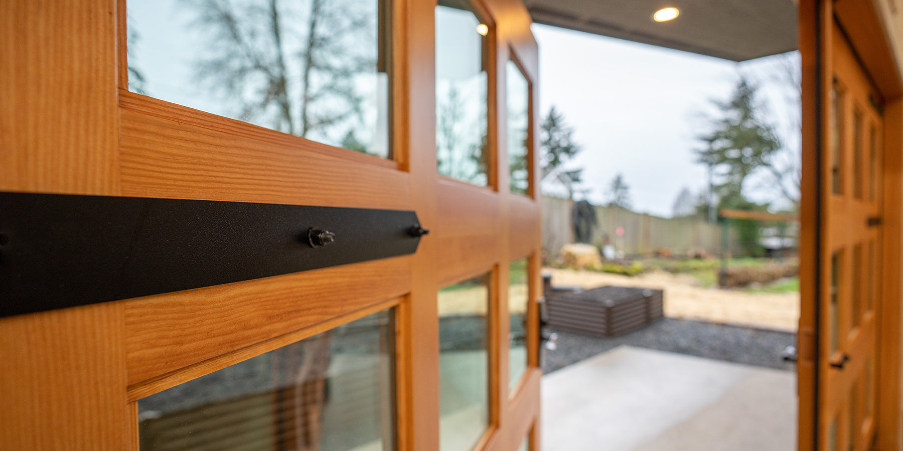 McIntyre Furniture woodshop exterior view featuring wood grain and strap hinges of the Douglas Fir Carriage Doors.