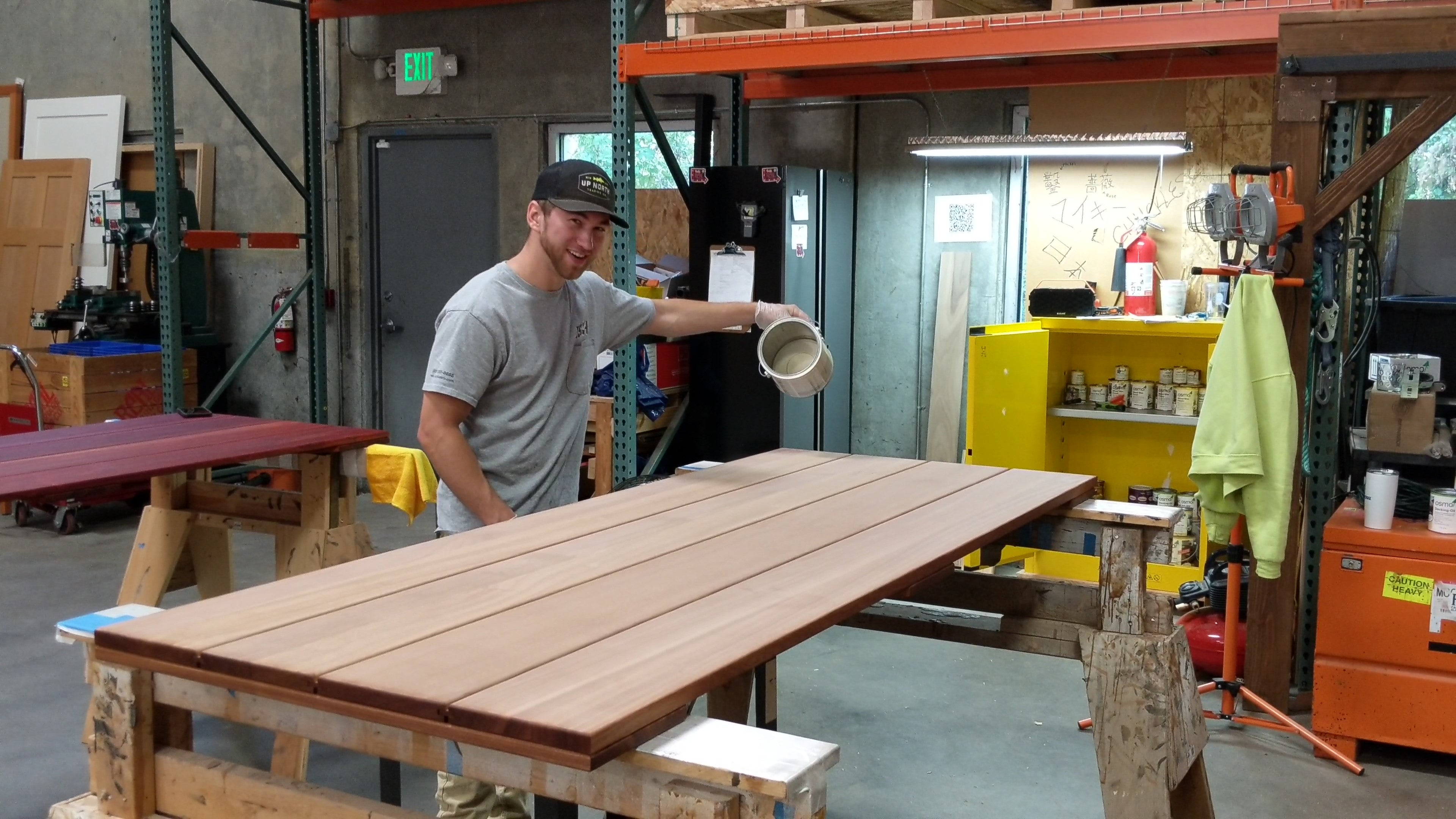 Michael applying wood finish to a sapele barn door