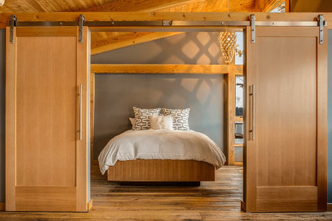 Solid Wood Bi-Opening Sliding Barn Doors Opening To A Light And Airy Bedroom With
