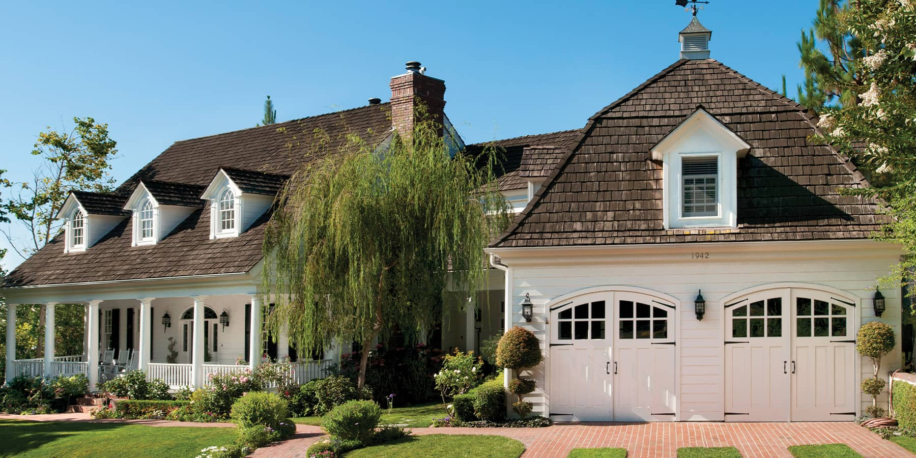 Exterior of a white home with a green garden area featuring 2 sets of white arched Carriage Doors by RealCraft.
