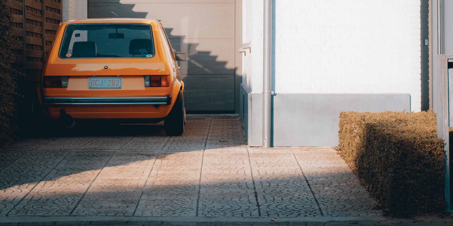 Clean home driveaway during sunset featuring a parked vintage yellow car.