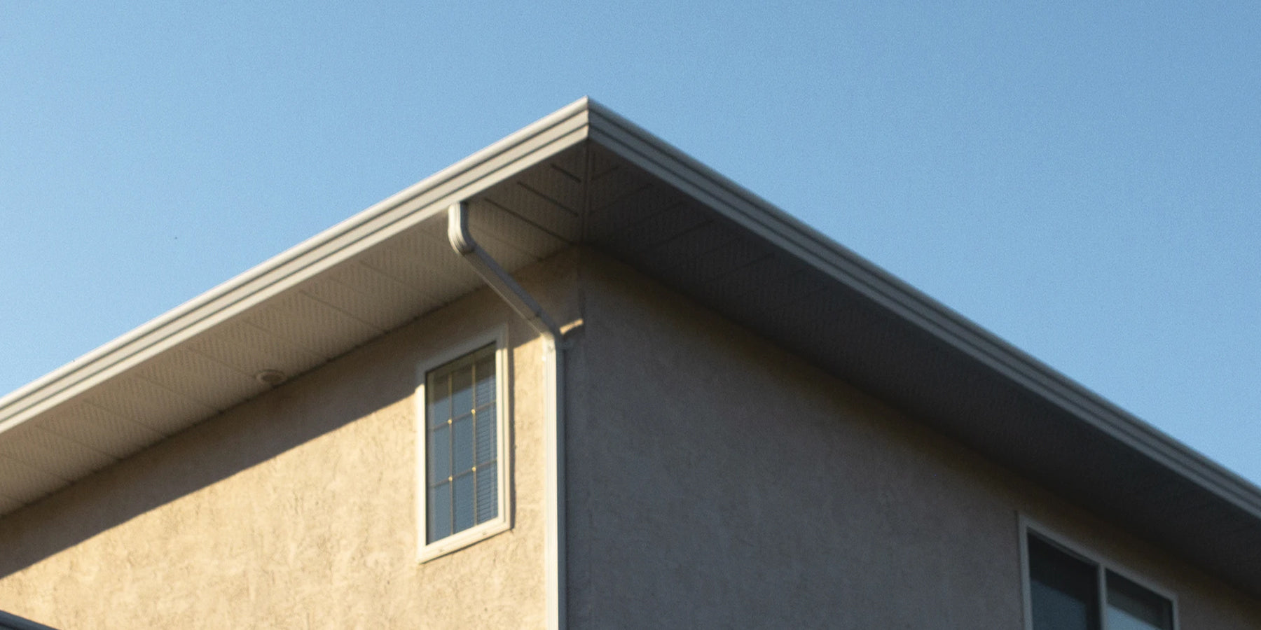 building facade with blue clear sky on the back. Shot highlights building's gutter system.