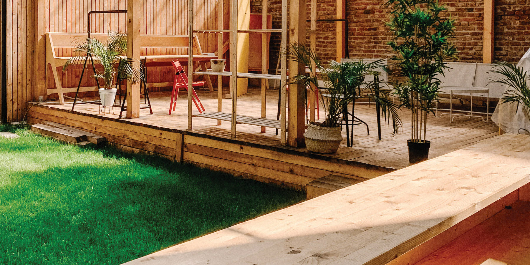 Exterior wooden porch area featuring seating areas, plants, and fresh green grass around it.