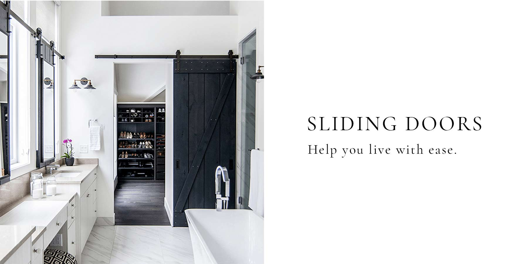 Traditional barn door design in black weathered wood installed in a luxurious closet space.