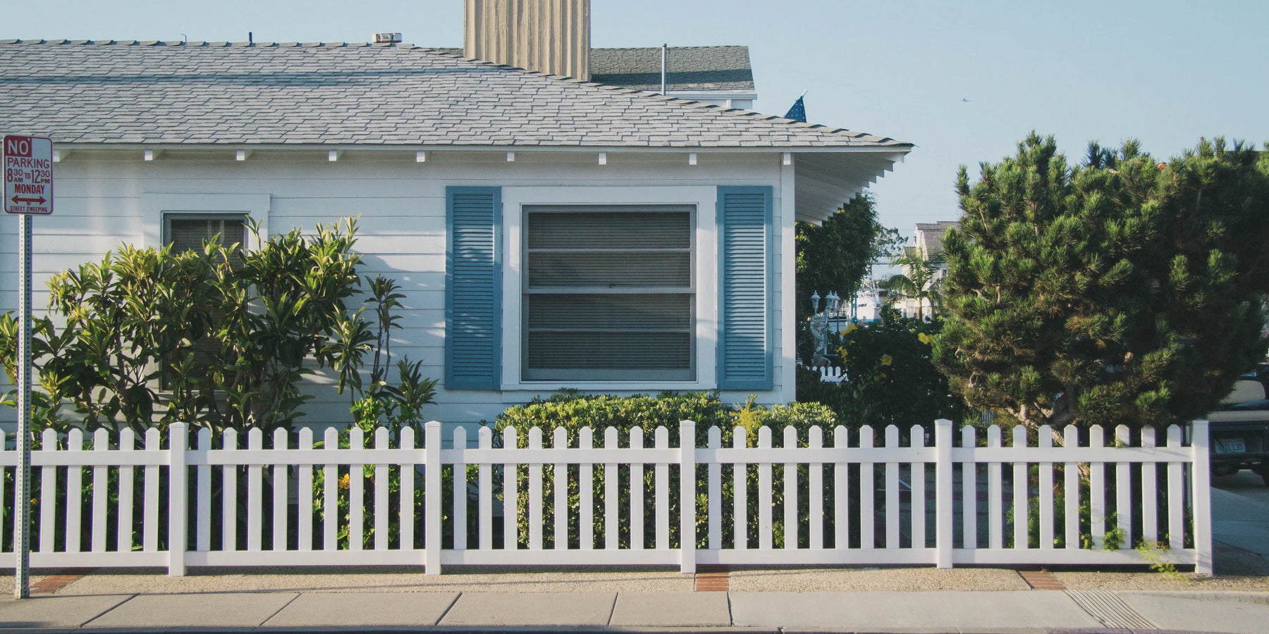 Street curbside corner featuring a white house with a open blue shutters and a white fence.