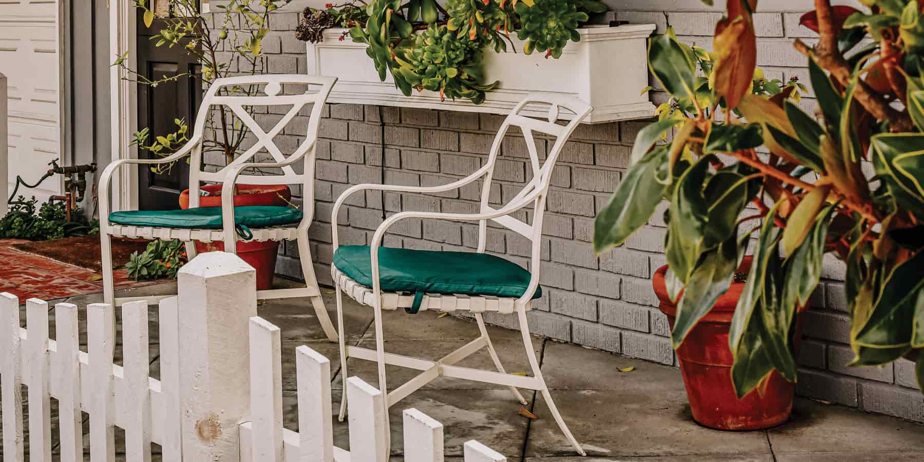 Two white chairs on a patio area with white fence around the porch.