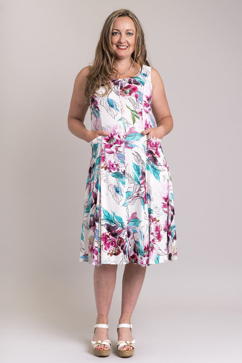 Women's white tropical flower print sleeveless knee-length dress with round neckline, front pleats, and pockets.
