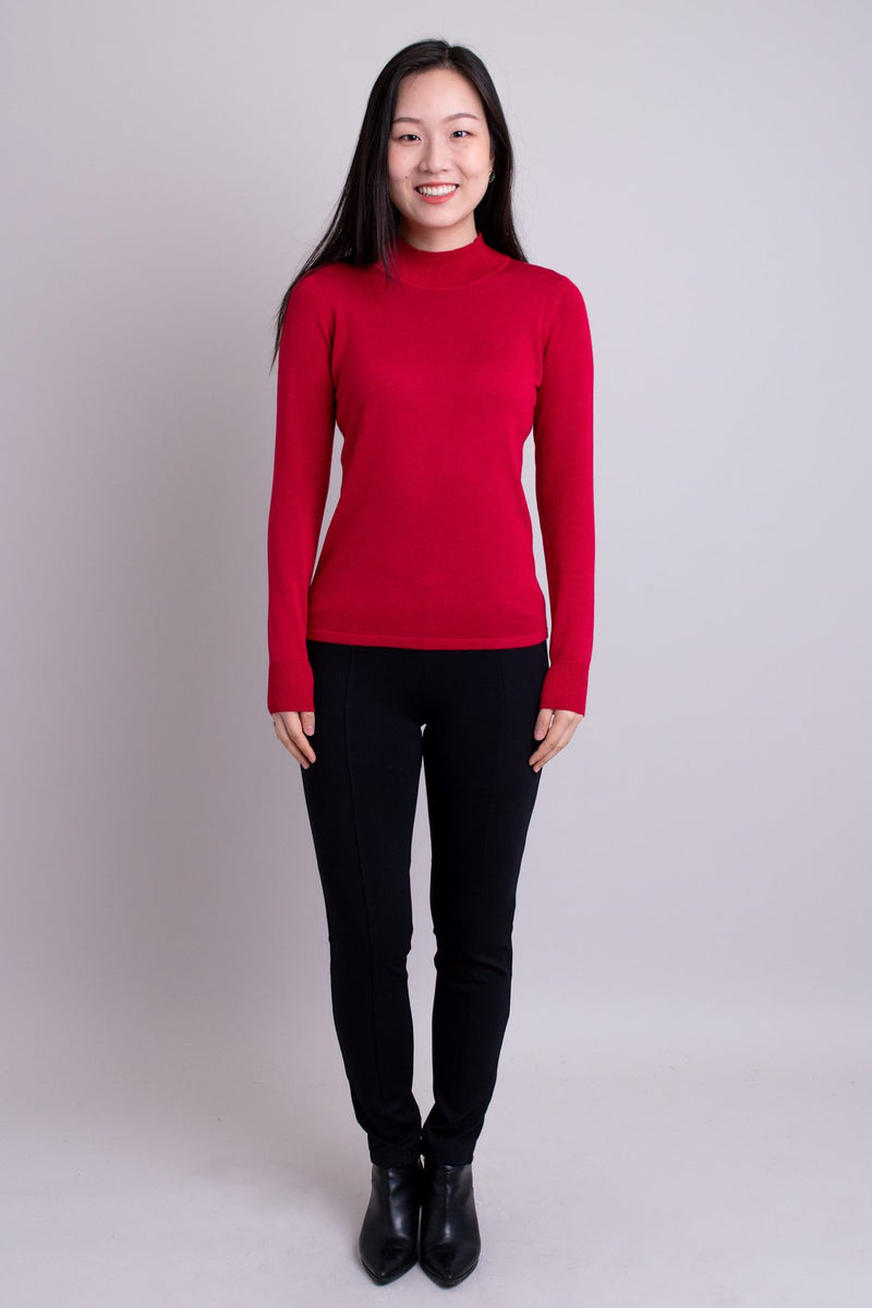 Women's red long-sleeve mock neck sweater worn with black pants. Made with sustainable and natural fibers, fair-trade.