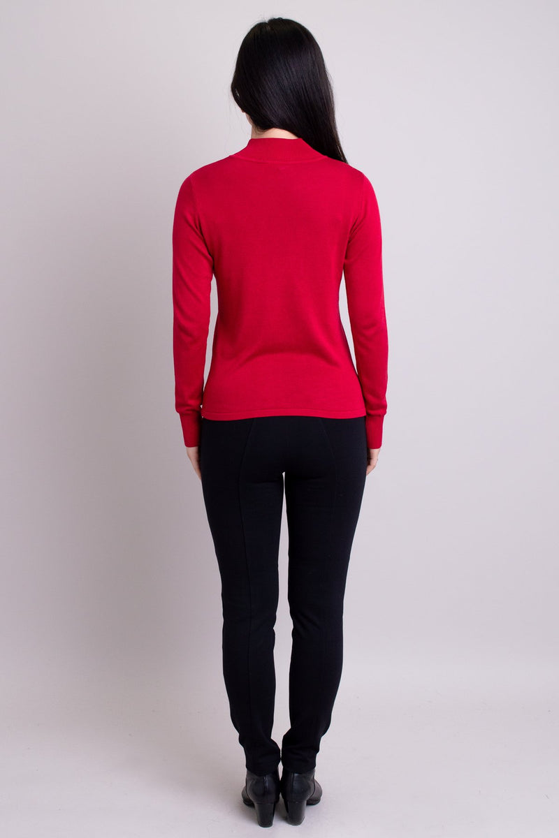 Women's red long-sleeve mock neck sweater worn with black pants. Made with sustainable and natural fibers, fair-trade. Back view.
