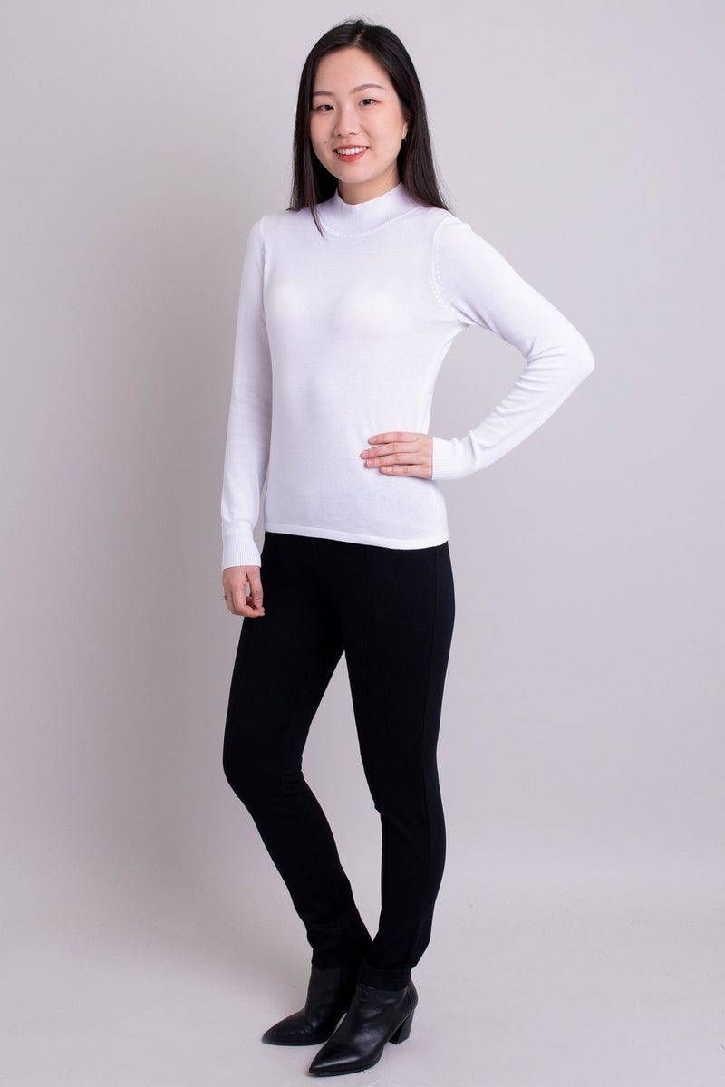 Women's white long-sleeve mock neck sweater worn with black pants. Made with sustainable and natural fibers, fair-trade.
