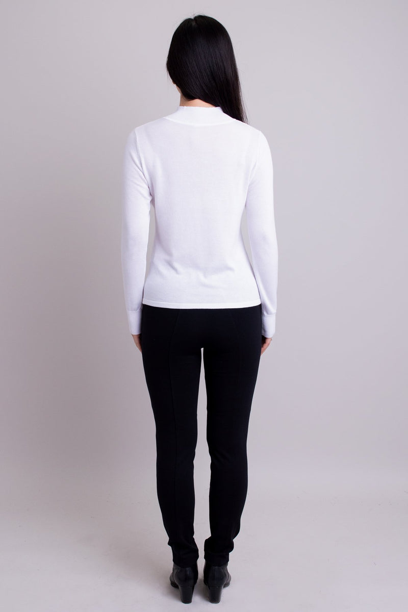 Women's white long-sleeve mock neck sweater worn with black pants. Made with sustainable and natural fibers, fair-trade. Back view.
