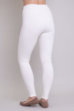 White, and comfy women's leggings with fleece interior. Made with sustainable and natural fibers, fair-trade, and available in plus-size. back view.