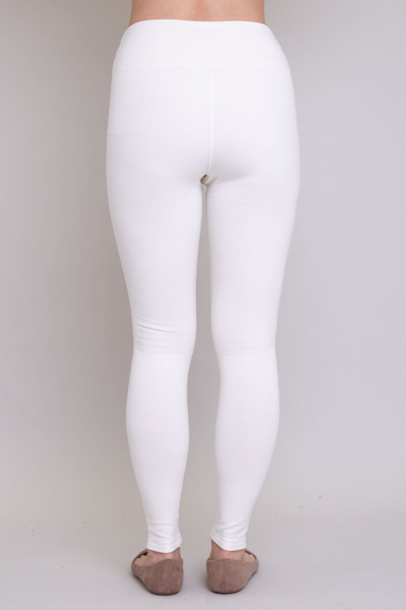 White, and comfy women's leggings with fleece interior. Made with sustainable and natural fibers, fair-trade, and available in plus-size. Full back view.
