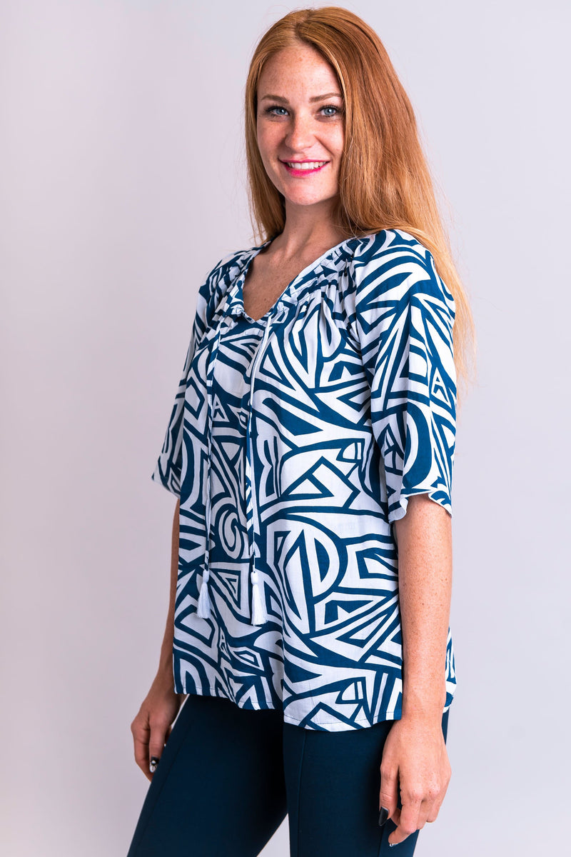 Women's tiki blue and white print bohemian 3/4 sleeve draped shirt with wide neckline.