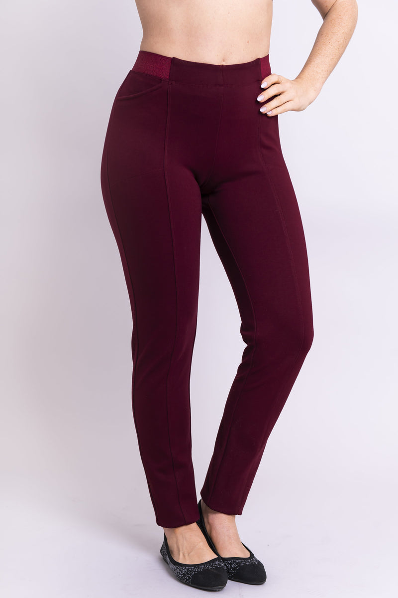 Hand on the hip view of women's petite burgundy tailored pant, with slim and narrow leg. Made of sustainable and natural bamboo fibers, fair-trade.
