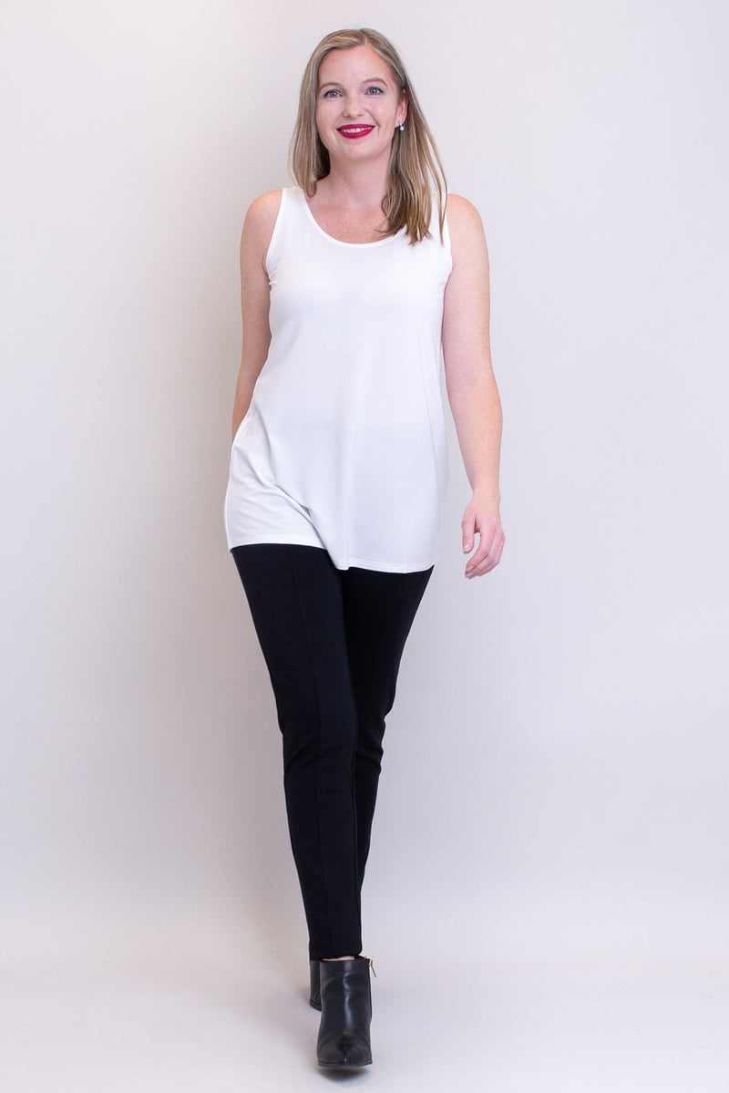 Women's plus-size casual white flowy tank top with wide shoulder strap and U-neckline, worn with black pants and boots.