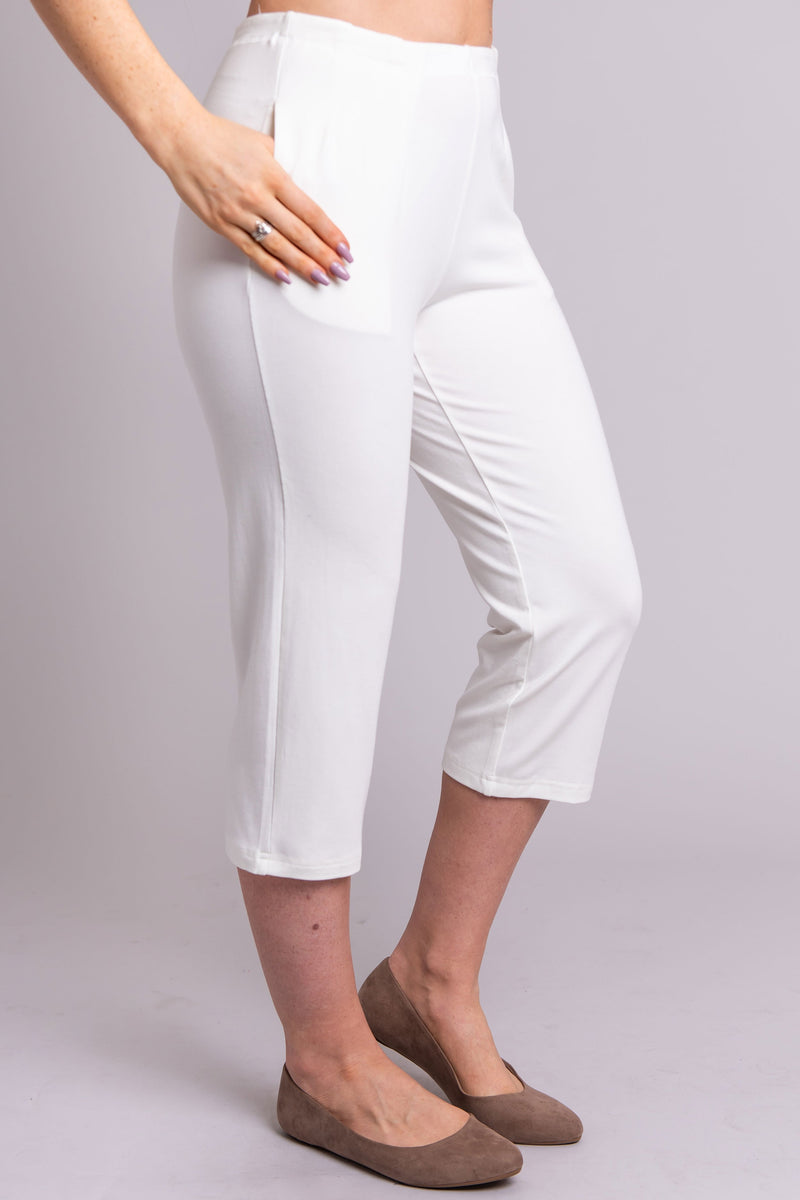 Women's white knee-length capri pants with pockets.