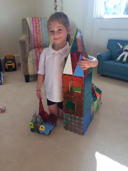 Proud of the Magna Tiles tower toy this little girl built.