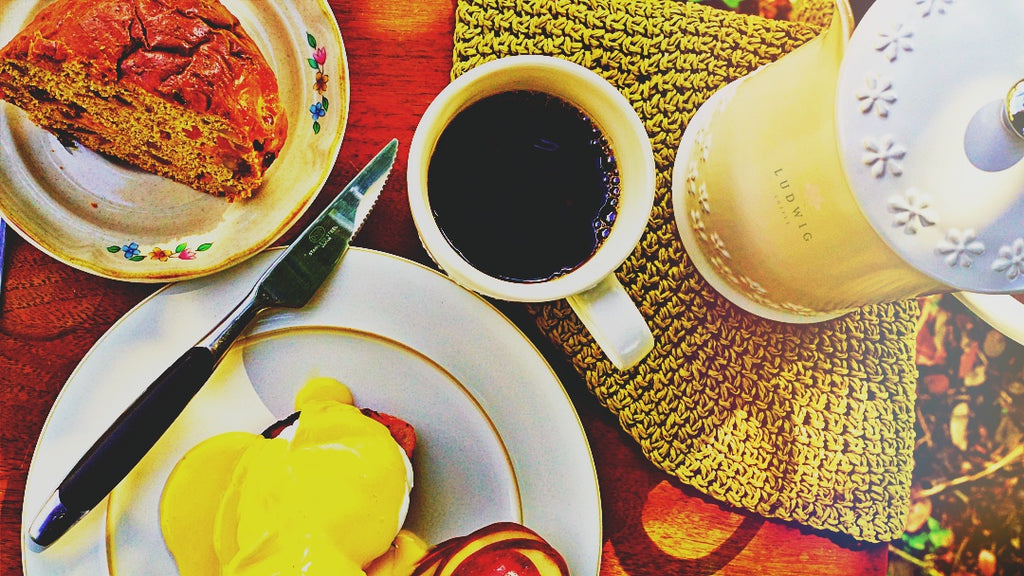 A breakfast table setup featuring Ludwig Coffee, Eggs Benedict, a loaf of bread and a coffee kettle